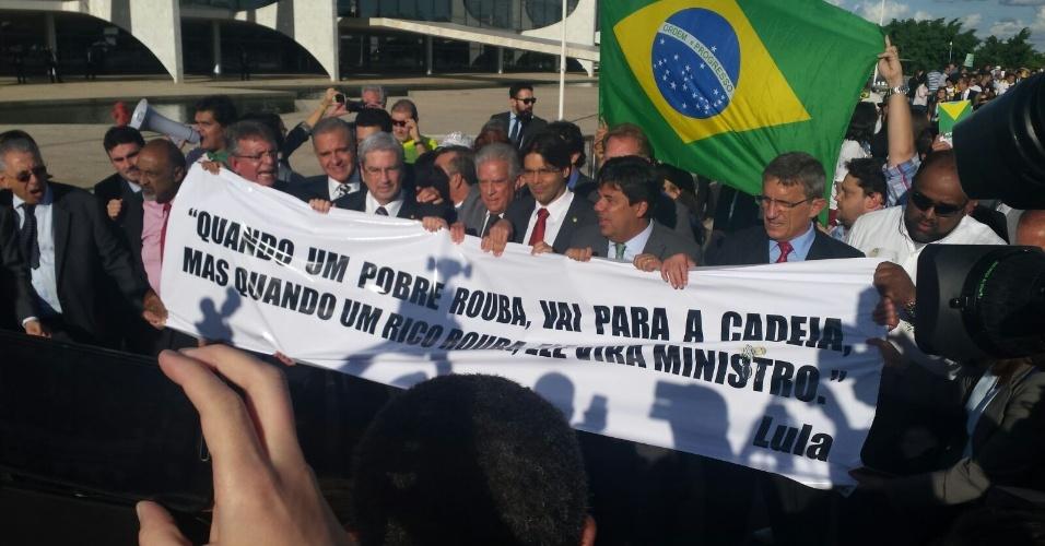 """16.mar.2016 - Deputados de oposição bloqueiam a entrada do Palácio do Planalto segurando uma faixa com uma frase de Lula de 1988: """"No Brasil é assim: quando um pobre rouba, ele vai para a cadeia, mas quando um rico rouba ele vira ministro"""""""