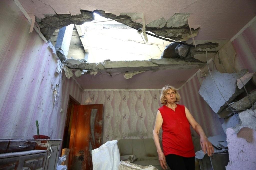 24.jun.2016 - Moradora da cidade ucraniana de Donetsk anda por sua casa que foi destruída por um bombardeio russo. Embaixadores da União Europeia concordaram em prorrogar por mais seis meses as sanções econômicas contra a Rússia devido à ausência de progresso para resolver o conflito na Ucrânia