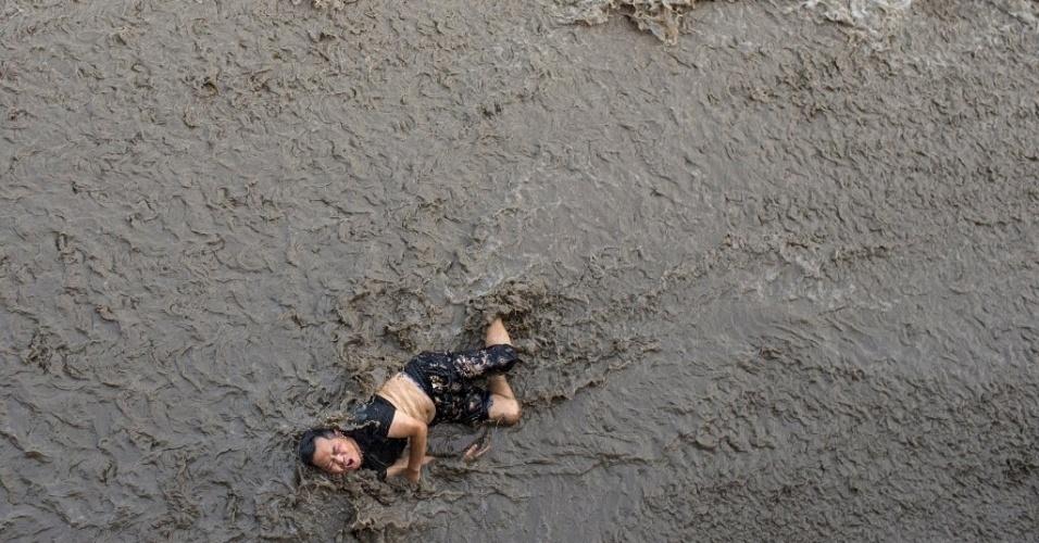 26.jul.2016 - Homem é surpreendido por uma onda às margens do rio Qiantang, em Hangzhou, na China. Ele estava observando o rio atrás de uma barreira de proteção, mas as ondas causadas pela maré alta ultrapassaram o muro e ele acabou caindo no rio