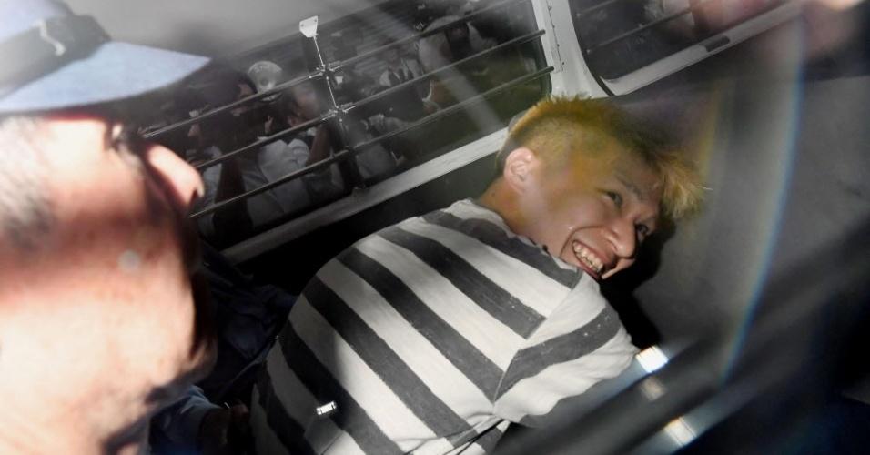 """27.jul.2016 - O japonês que confessou ter assassinado 19 pessoas em um centro para deficientes mentais sorriu ao ser fotografado pela imprensa enquanto chegava para um interrogatório. A polícia revistou a casa de Satoshi Uematsu, que defendia que """"pessoas com problemas mentais deviam desaparecer"""""""
