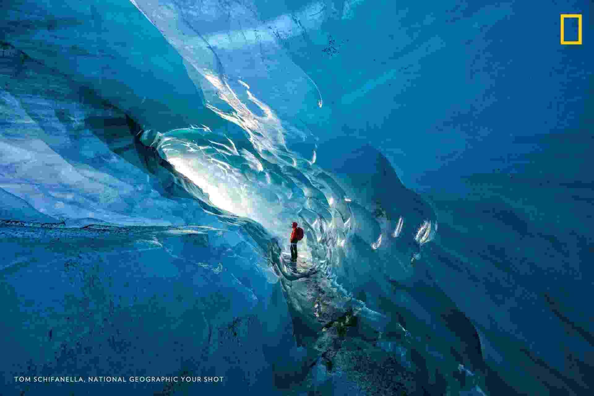 Guia na Islândia admira uma das cavernas de gelo do país. A personagem da foto entra na caverna há anos e afirma que, desde 2000, a área livre vem se expandido por causa do aquecimento global. Em menos de 15 anos, as geleiras da Islândia perderam 12% de seu tamanho - Tom Schifanella/National Geographic Your Shot