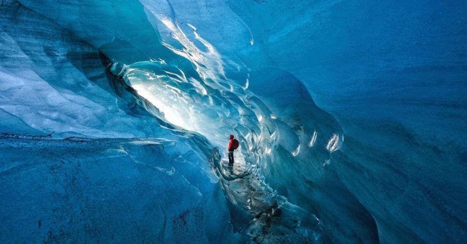 Guia na Islândia admira uma das cavernas de gelo do país. A personagem da foto entra na caverna há anos e afirma que, desde 2000, a área livre vem se expandido por causa do aquecimento global. Em menos de 15 anos, as geleiras da Islândia perderam 12% de seu tamanho