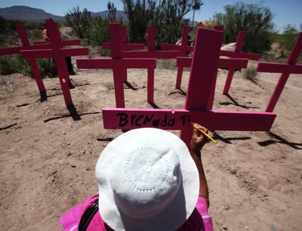 Mulher pinta o nome da filha em cruz cor de rosa em Arroyo del Navajo, no Vale Juarez (México)