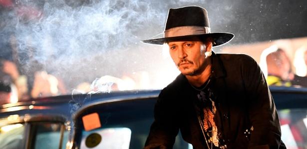 """O ator Johnny Depp posa sobre um Cadillac antes da apresentação de seu filme """"The Libertine"""" no festival Glastonbury, no Reino Unido"""