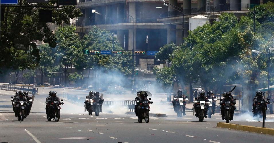 30.jul.2017 - Policiais passam por nuvem de gás lacrimogêneo