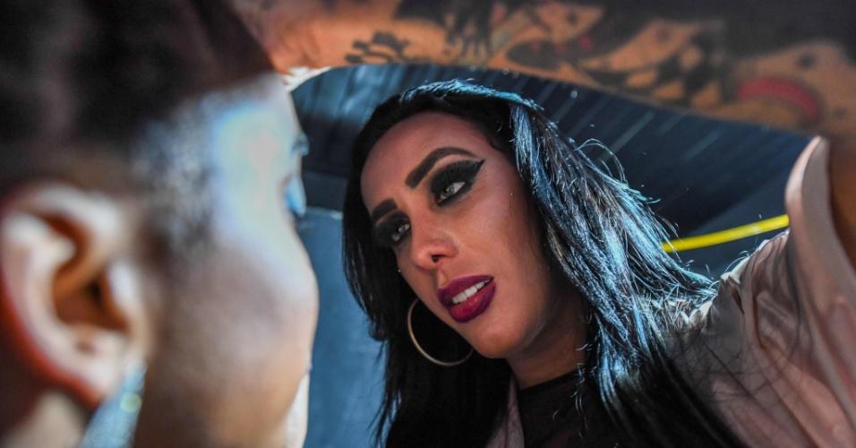 A cantora de funk transgênero MC Trans maquiando um de seus dançarinos antes de fazer apresentação em clube noturno na favela da Rocinha, no Rio de Janeiro