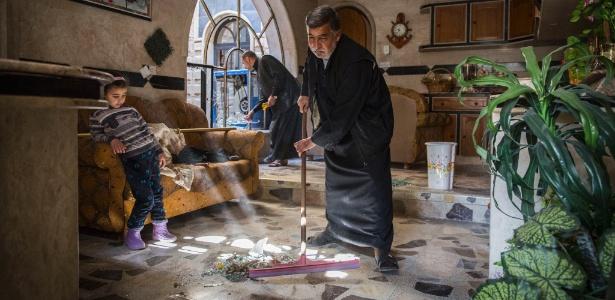 25.mar.2017 - Família faz limpeza após retornar para casa. O local sofreu estragos após a explosão de um carro-bomba usado pelo Estado Islâmico, em Mossul, Iraque