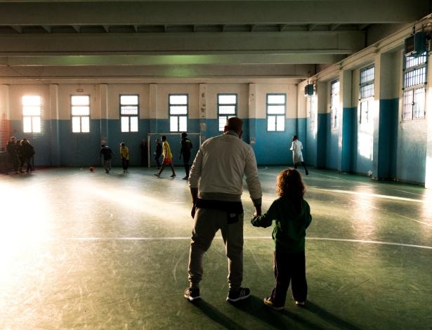 Pais com seus filhos durante uma partida de futebol na prisão Opera em Milão