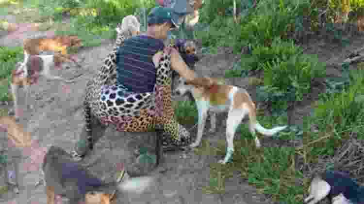 Um dos acusados compartilhou foto em grupo na qual se mostra carregando a onça que matou, acompanhado dos cachorros que o ajudaram na caçada ilegal - Reprodução/MPF