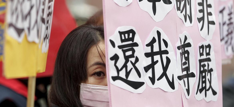"""31.dez.2015 - """"Japão se desculpe. Restaure minha dignidade"""", diz cartaz exibido por mulher durante protesto em frente à embaixada do Japão em Taiwan - Pichi Chuang/Reuters"""