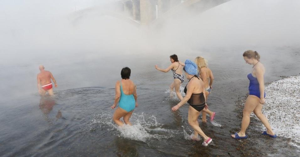 """6.jan.2015 - Mulheres entram na água gelada do rio Yenisei, em Krasnoyarsk, na Sibéria (Rússia). Quem encabeça o grupo é Mikhail Sashko (esq.), líder e um dos fundadores do clube Cryophile, que reúne praticantes de natação no frio do inverno siberiano. A temperatura atmosférica no momento em que os banhistas entravam na água era de -27°C. """"O momento de imersão na água é uma sensação de prazer. Depois disso, ocorre uma descarga de energia e meu corpo inteiro se sente relaxado"""", diz Sashko"""