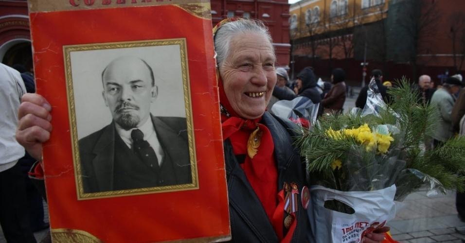 22.abr.2016 -  Idosa carrega flores e um cartaz com a foto de Vladimir Lenin durante cerimônia na qual pessoas depositam flores no mausoléu do ex-estadista e líder comunista russo, em Moscou. O ato marca o 146º aniversário do nascimento de Lenin
