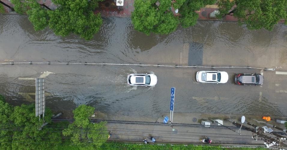 2.jun.2016 - Carros atravessam rua alagada em Nanchang, no leste da China, atingida por fortes chuvas que causaram enchentes em diversos pontos da cidade