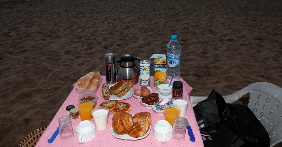 4.jul.2016 - Para quebrar o jejum, eles levaram doces, ovos e pizza e colocaram sobre a mesa instalada na areia da praia