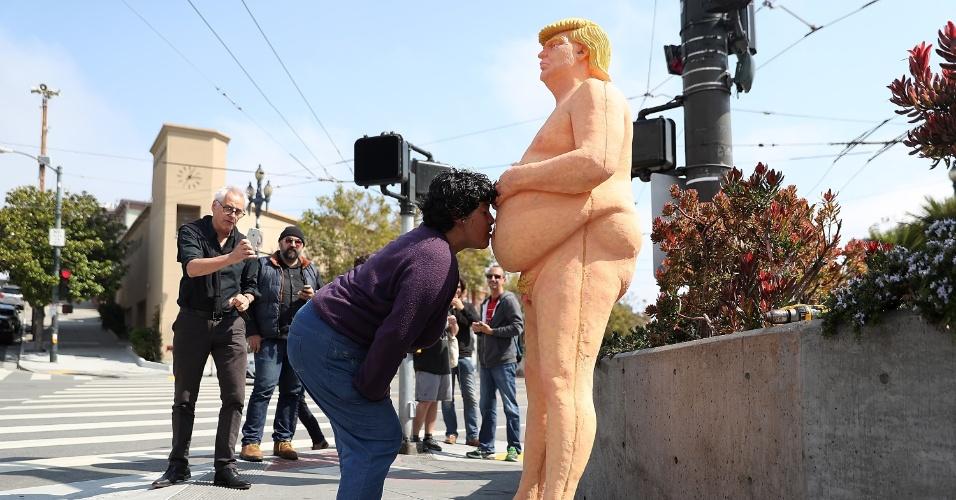 18.ago.2016 - Pedestre beija a barriga da estátua de Donald Trump, em San Francisco
