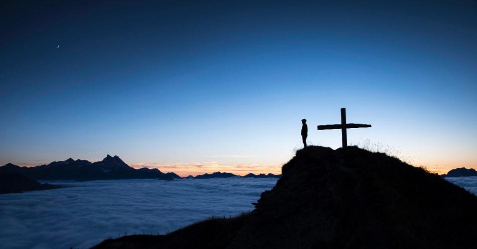 6.out.2016 - Homem observa o mar de nuvens, durante o pôr do sol no topo da montanha Croix des Chaux/Chaux Ronde (2012 metros de altitude) em Gryon VD, na Suíça