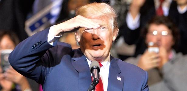 O presidente eleito dos EUA Donald Trump bloqueia a luz para ver o público durante evento em Fayetteville, que faz parte do tour de agradecimento pela vitória nas eleições dos EUA