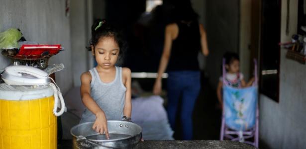 Uma das filhas de Yennifer Padron e Victor Cordova brinca com a água em uma panela na casa que eles vivem na favela Petare, em Caracas