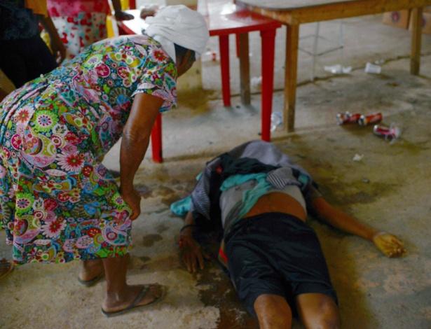 Mulher olha um dos corpos atingidos pelo tiroteio que ocorreu no vilarejo La Concepción, em Acapulco, no estado de Guerrero, no México