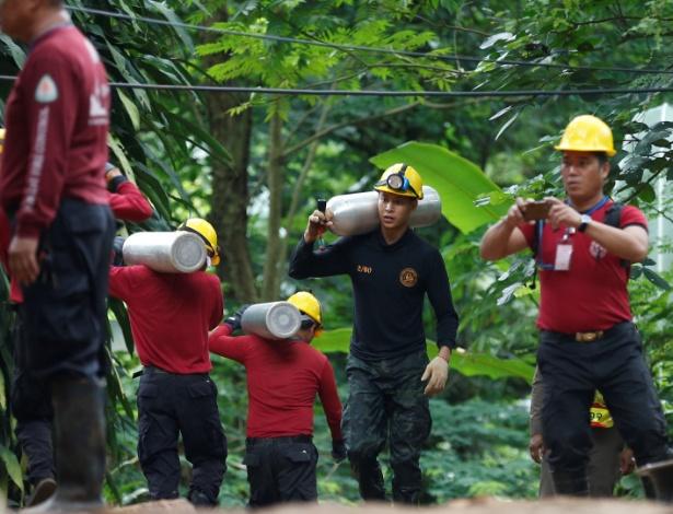 Socorristas carregam cilindros de oxigênio neste sábado nas proximidades da caverna - Soe Zeya Tun/Reuters
