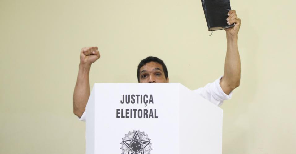 Na cabina de votação, o candidato Cabo Daciolo levanta uma bíblia. Ele chegou para votar acompanhado da mulher e dos filhos na região do Recreio dos Bandeirantes, no Rio de Janeiro