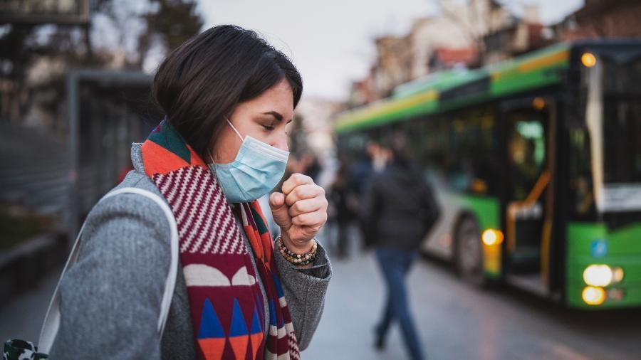 Mulher usa máscara de proteção - iStock