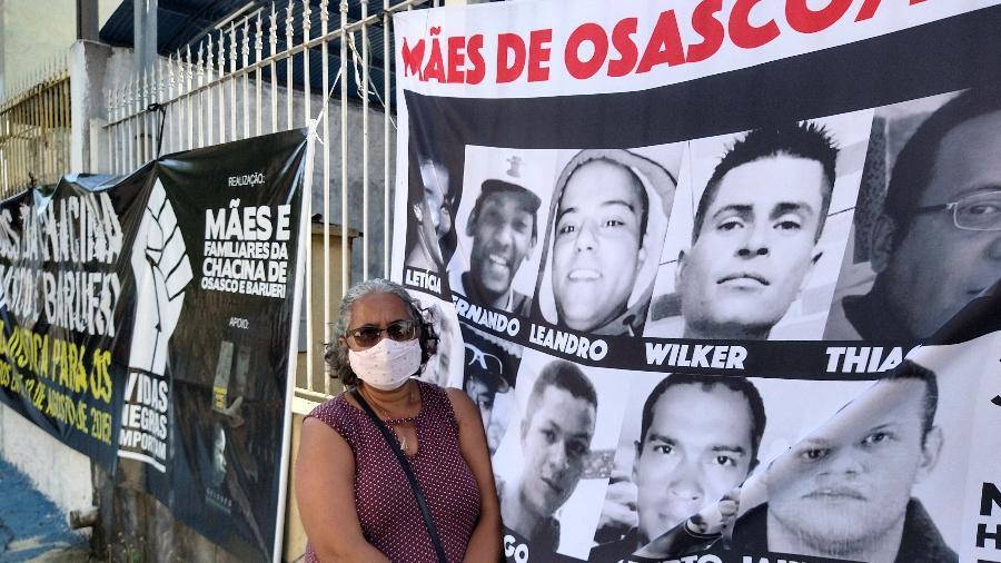 A professora Aparecida Gomes da Silva Assunção, 59, posa ao lado de faixa com fotos de 11 vítimas da chacina; ela é mãe do mecânico industrial Leandro Pereira Assunção, morto aos 36, e pretende acompanhar o julgamento até o final - Marcelo Oliveira/UOL