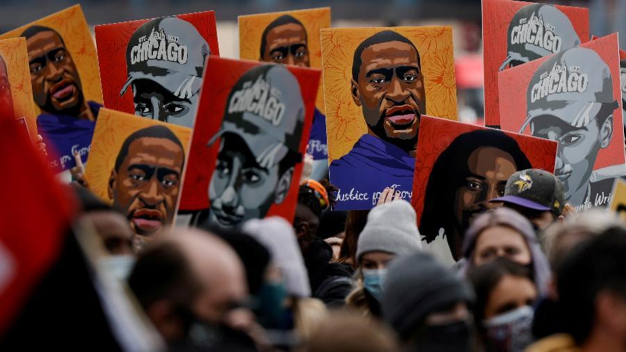 20.abr.2021 - Pessoas seguram cartazes com pinturas de George Floyd após a condenação de Derek Chauvin - Carlos Barria/Reuters
