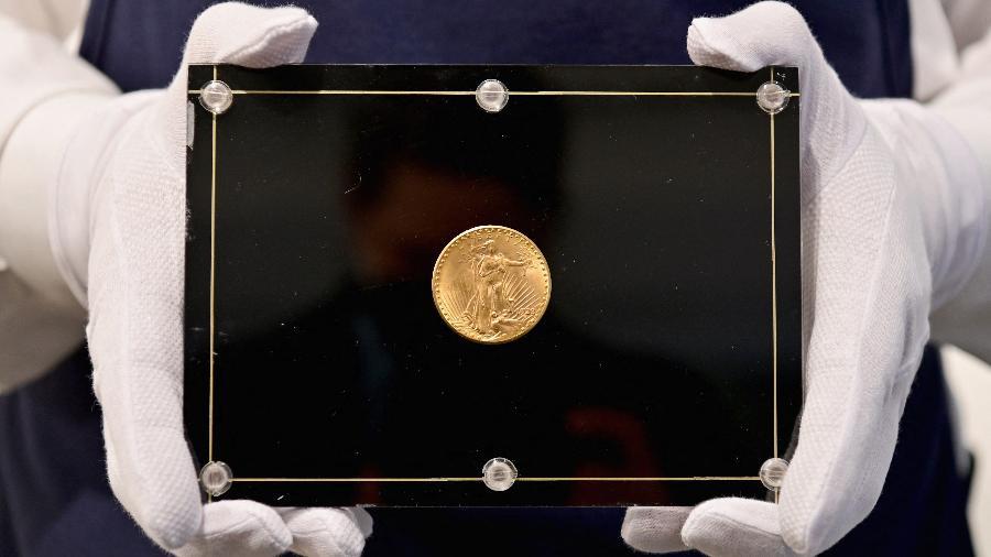 """Um funcionário da Sotheby""""s segura uma moeda Double Eagle de 1933 durante um leilão ao vivo; peça faz parte da última série de moedas de ouro - Angela Weiss / AFP"""