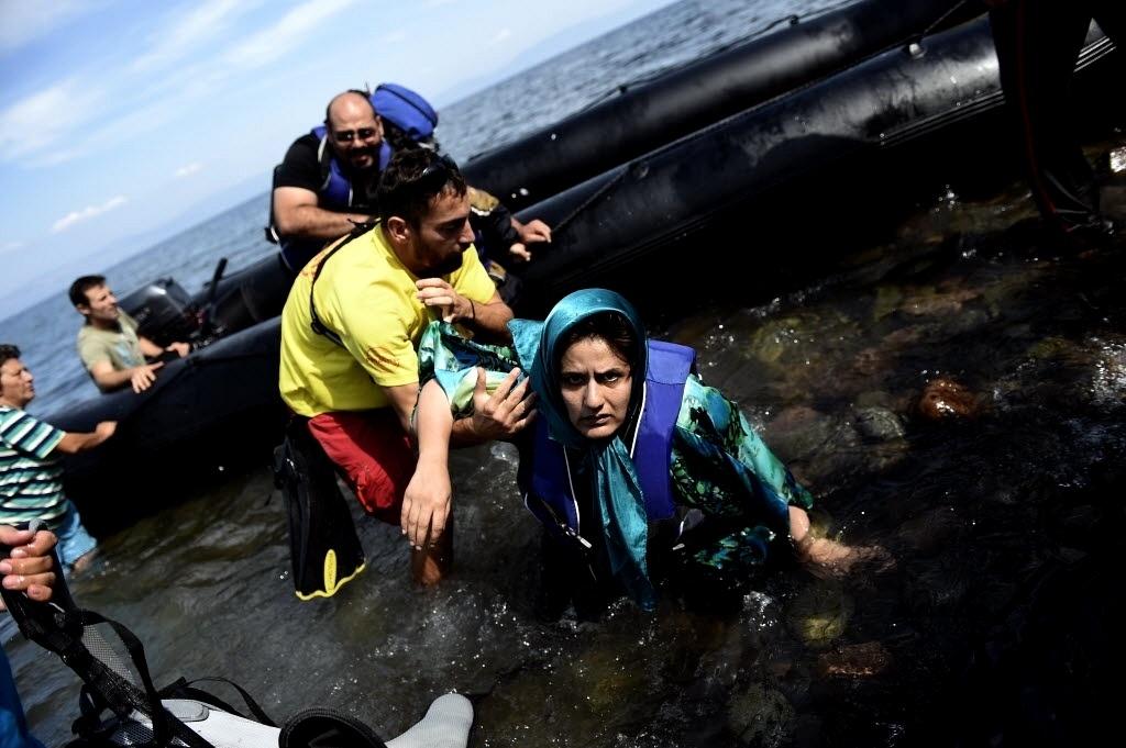 27.set.2015 - Homem ajuda mulher a sair de barco de refugiados que saiu da Turquia, cruzou o mar Egeu e chegou à ilha grega de Lesbos neste domingo (27). Na mesma travessia, 17 sírios, incluindo cinco mulheres e cinco crianças, morreram afogados quando o barco em que viajavam naufragou, segundo a agência de notícias turca Dogan