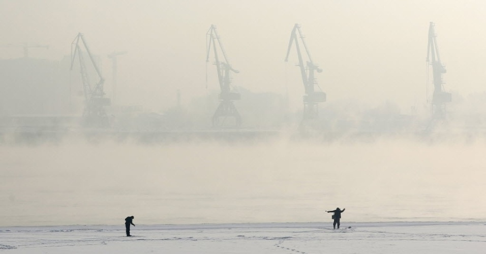 30.jan.2016 - Russos pescam no rio Yenisei, coberto de gelo, com o porto da cidade de Krasnoyarsk ao fundo. A temperatura na cidade da Sibéria neste sábado chega a 24 graus negativos