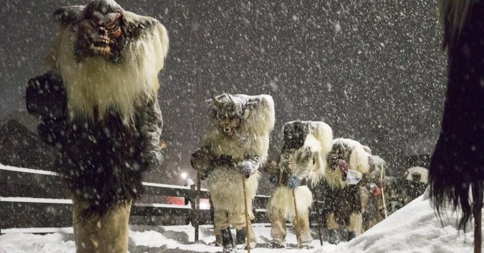 """5.fev.2016 - """"Tschaeggaettaes"""", nome pelo qual são conhecidos os participantes mascarados do carnaval da Suíça, desfilam sob a neve, em chão coberto de gelo, em Blattern, no vale suíço de Loetschental. Os """"Tschaeggaettaes"""" usam roupas de pele animal e tem como objetivo assustar as pessoas, lembrando o folclórico personagem """"Clóvis"""", ou """"Bate-bolas"""", do carnaval brasileiro, que também usa roupa extrevagante e sai na rua pregando peças"""