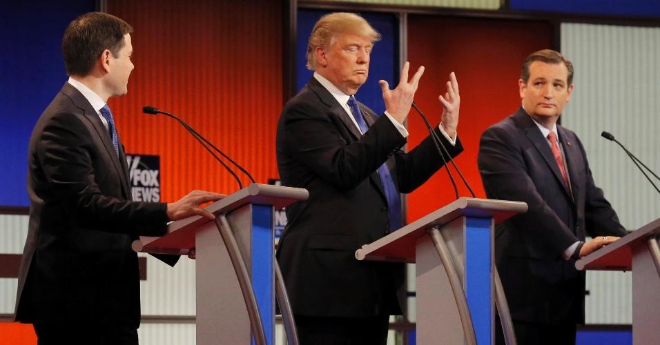 """4.mar.2016 - Em debate nesta quarta-feira (3) entre os pré-candidatos republicanos para a eleição presidencial nos Estados Unidos, em Detroit, Donald Trump exibe as mãos após Marco Rubio (à esq.) insinuar que elas mostram tamanho de seu órgão genital. Rubio tem zombado de Trump em seus comícios dizendo que ele tem as mãos pequenas """"e vocês sabem o que isso significa..."""" """"Olhem para as minhas mãos. Elas são normais"""", disse. """"No resto, eu garanto"""", acrescentou o magnata"""