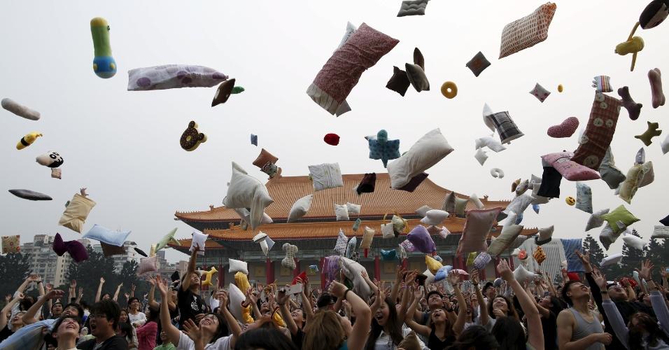 """2.abr.2016 - Pública atira travesseiros e almofadas para o alto durante o chamado """"dia internacional da guerra de travesseiros"""" na Praça da Liberdade, em Taipei, Taiwan"""