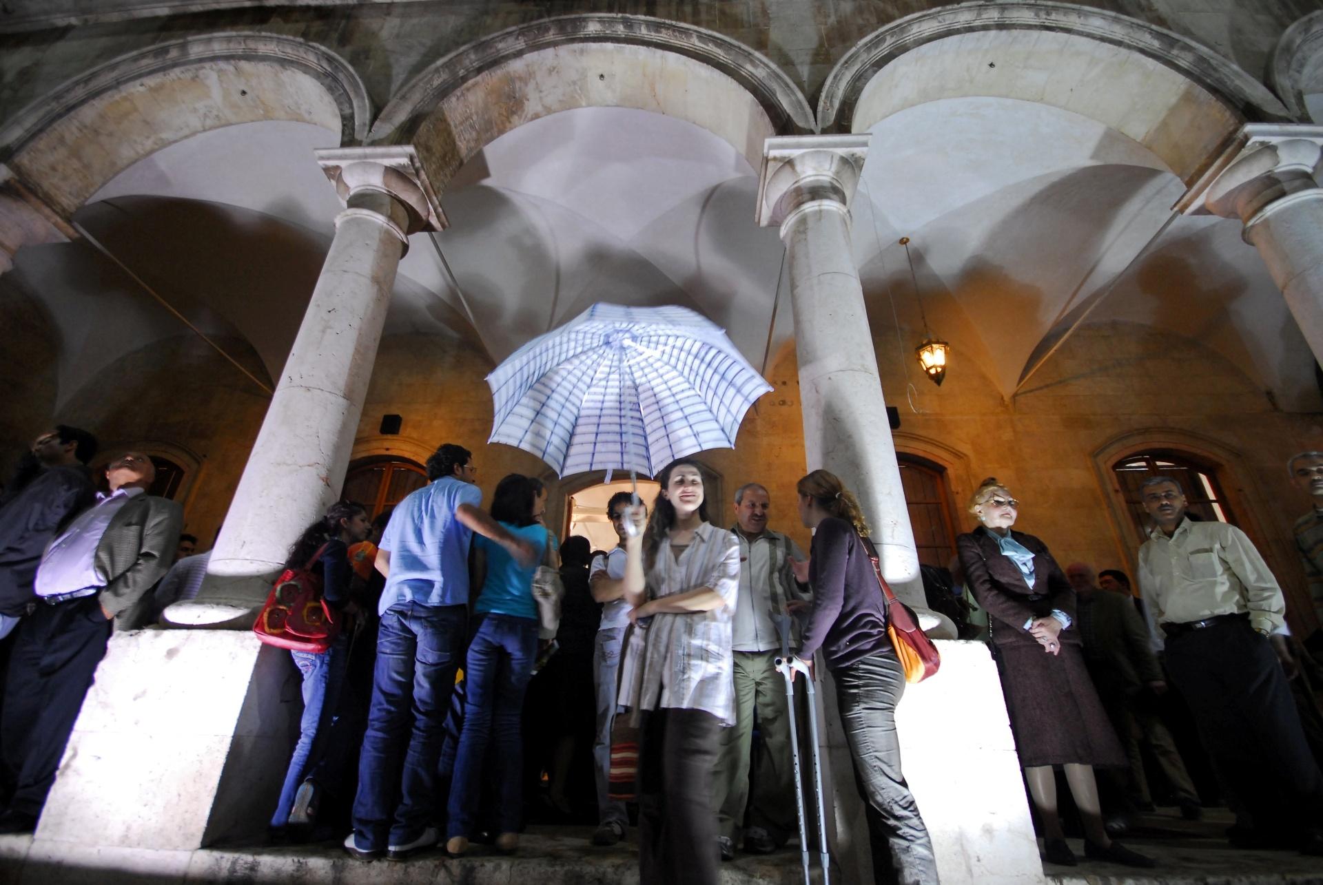 22.dez.2016 - Mulher brinca com guarda-chuva na entrada da escola de al-Sheebani, na Cidade Velha de Aleppo, Síria. A fotografia foi feita em 2008. Com a guerra, a cidade passou a ser dividida entre o governo e rebeldes, mas o exército manteve o controla da Cidade Velha mesmo quando estava cercada por insurgentes dos três lados e o único acesso era por um túnel