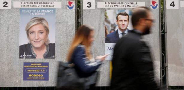10.abr.2017 - Pessoas passam por cartazes eleitorais de Marine Le Pen, da Front Nacional, e de Emanuel Macron, do En Marche!, em Paris (França)