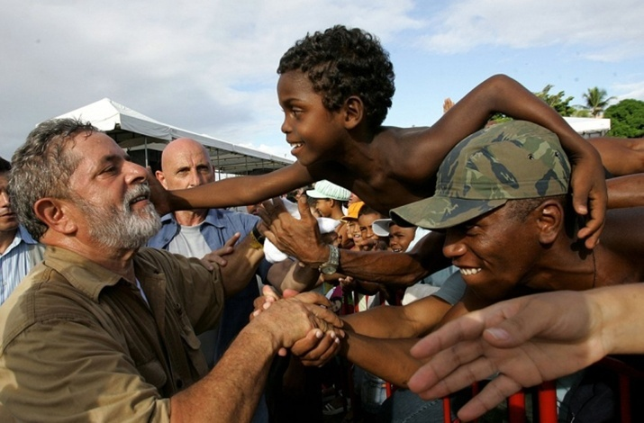 Garoto Everton Conceição Santos, então com sete anos, se aproxima do presidente Lula, em Lauro de Freitas, na Bahia, em 2006
