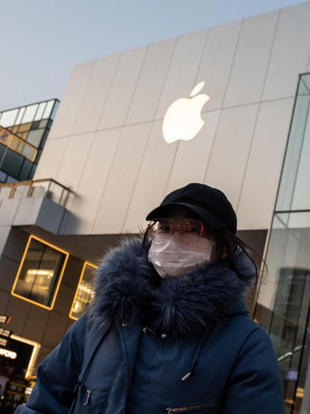 Mulher usa máscara de proteção em frente a uma loja da Apple em Beijing, na China - Nicolas Asfouri/AFP
