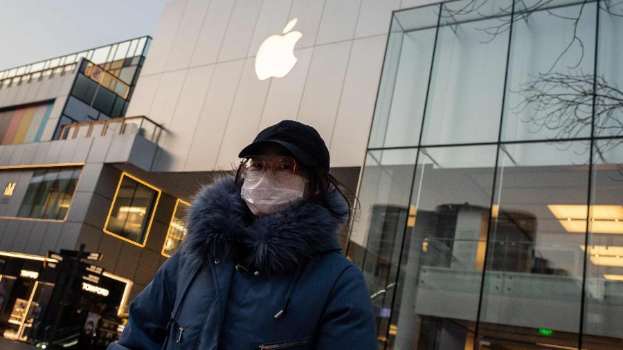 Coronavírus: Mulher usa máscara de proteção em frente a uma loja da Apple em Beijing, na China - Nicolas Asfouri/AFP