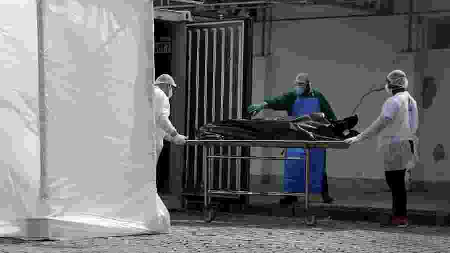 Profissionais de saúde com trajes de proteção transportam cadáver para caminhão frigorífico durante pandemia de Covid-19 no Rio de Janeiro -