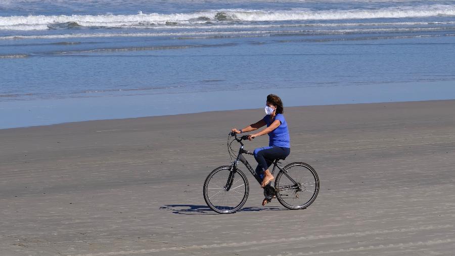 29.mai.2020 - De máscara, moradora anda de bicicleta na praia da Baleia, em São Sebastião, litoral norte de São Paulo - Marcello Zambrana/AGIF/Estadão Conteúdo