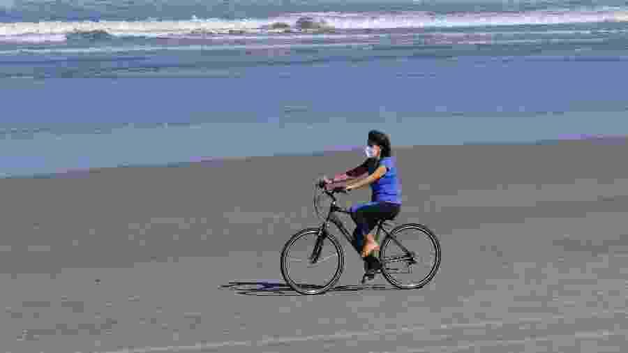 De máscara, moradora anda de bicicleta na praia da Baleia, em São Sebastião, litoral norte de São Paulo - Marcello Zambrana/AGIF/Estadão Conteúdo