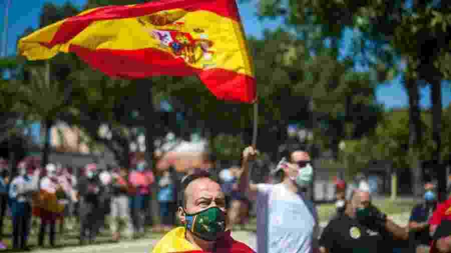 30.mai.2020 - De máscara e enrolado em uma bandeira, homem participa de marcha de apoio à Guarda Civil da Espanha, em Málaga - Jesus Merida/SOPA Images/LightRocket via Getty Images