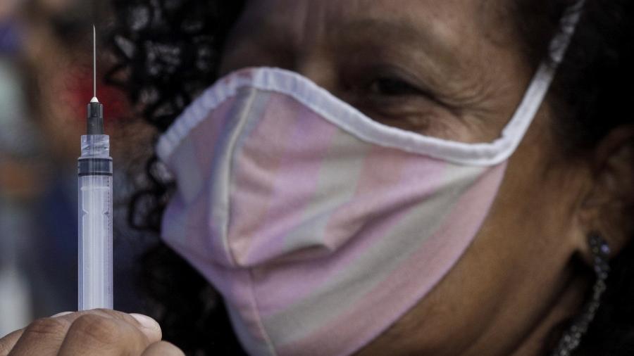 Profissional de saúde mostra seringa a paciente antes de aplicar dose da vacina da AstraZeneca contra a covid-19 - RICARDO MORAES/REUTERS