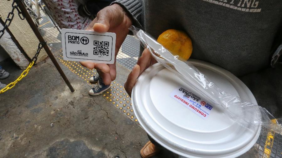 2 jun. 2020 - Marmita e QR Code na mão de pessoa em situação de rua em unidade da rede de restaurantes populares Bom Prato, em São Paulo - Sergio Andrade/Governo do Estado de São Paulo
