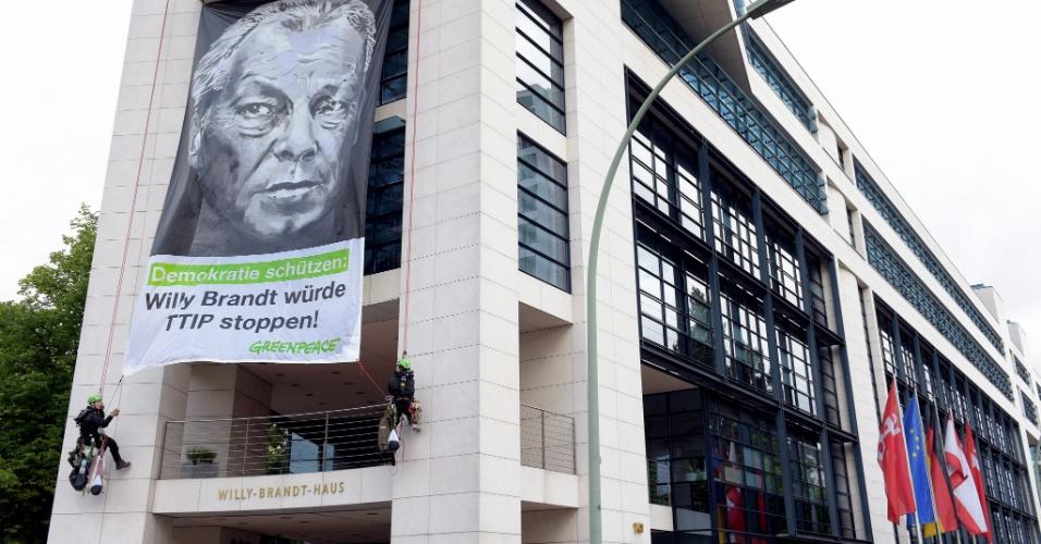 20.jun.2015 - Ativistas do Greenpeace penduram faixa com a frase