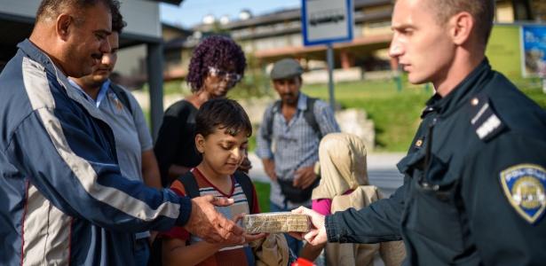 Policial croata oferece comida e água a migrantes na fronteira com a Eslovênia