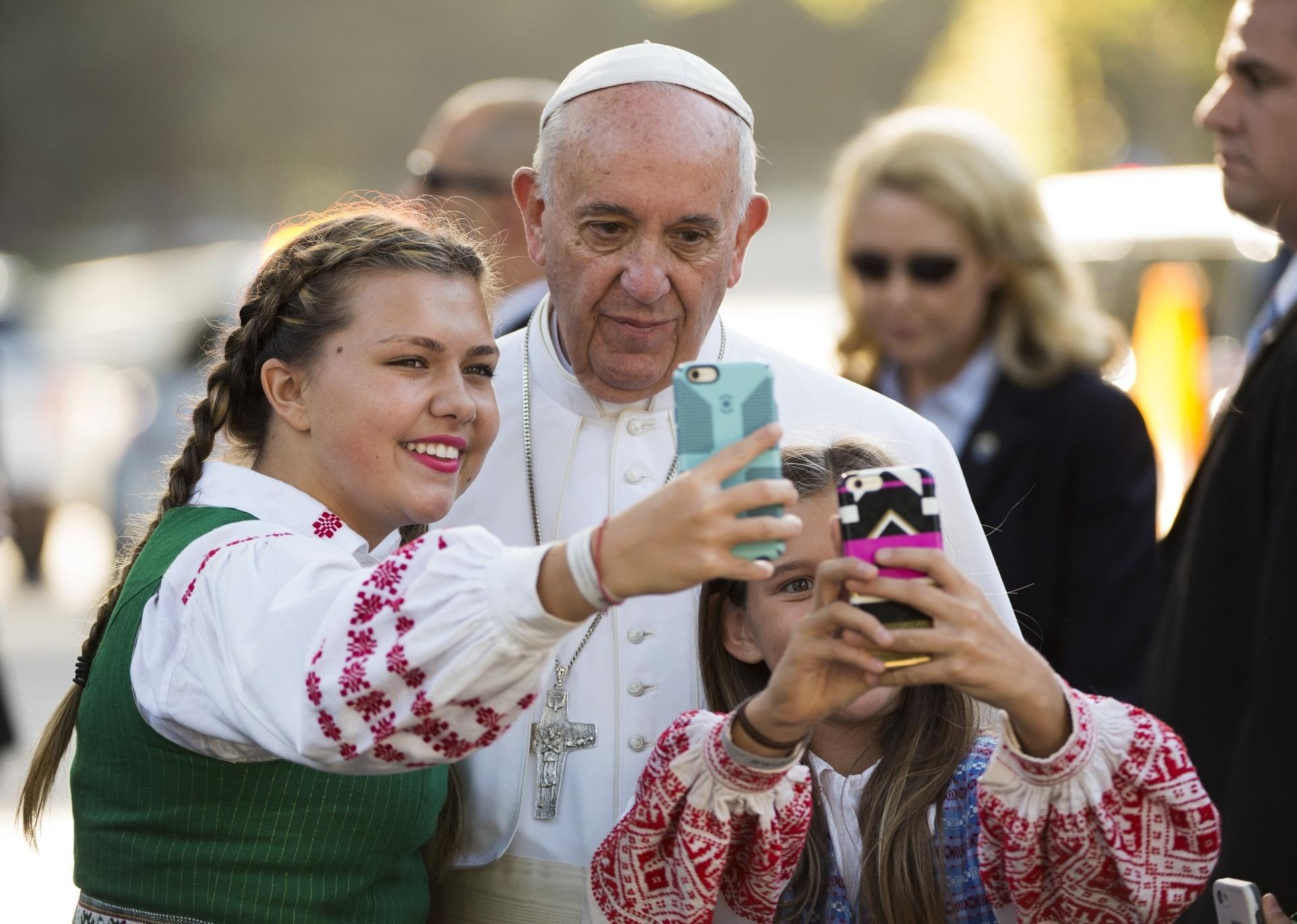 23.set.2015 - Papa Francisco tira uma foto com crianças cujos pais trabalham na Embaixada da Lituânia, em Washington, DC, nos Estados Unidos. O pontífice vai se encontrar com o presidente Barack Obama na Casa Branca onde devem discutir, entre outros temas, imigração, embargo econômico de Cuba e aquecimento global