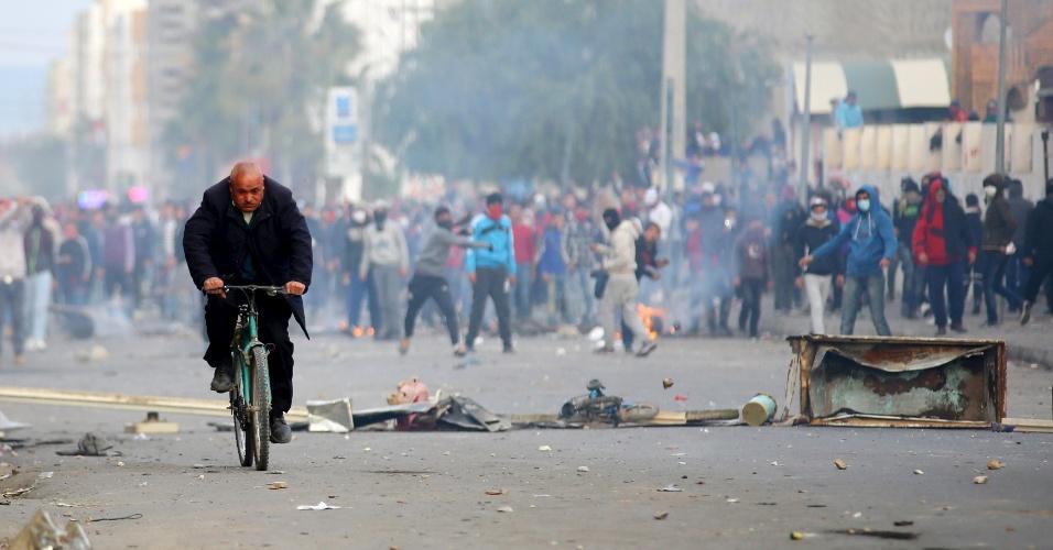 21.jan.2016 - Homem anda de bicicleta enquanto manifestantes atiram pedras contra a polícia durante protesto do lado de fora do escritório governamental local, em Kasserine, na Tunísia. Milhares de jovens foram às ruas após a morte de um jovem que supostamente se matou depois de recusar um emprego público