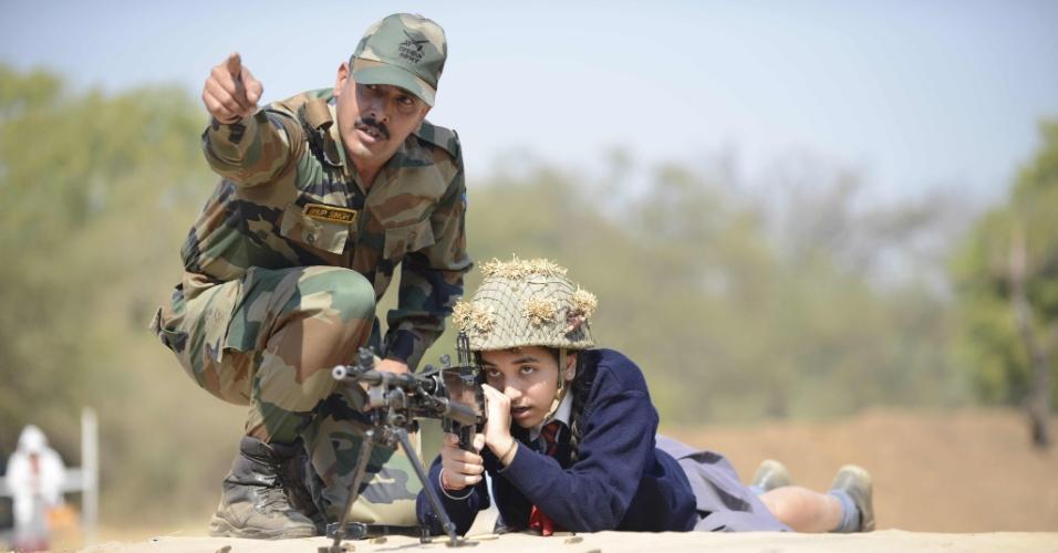 25.jan.2016 - Um soldado indiano ajuda uma garota em idade escolar enquanto ela se prepara para atirar uma arma durante uma demonstração nas redondezas da cidade de Gandhinagar, na Índia. O país asiático tem várias atrações especiais na véspera do Dia da República, entre elas esta realizada por membros das Forças Armadas
